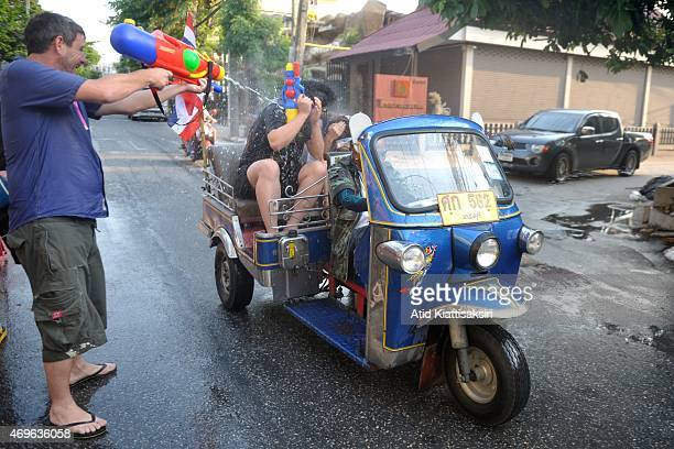 Couple in the back of a Tuk Tuk are sprayed with water during the Songkran festival at Tapae street The Songkran festival is the traditional Thai new...