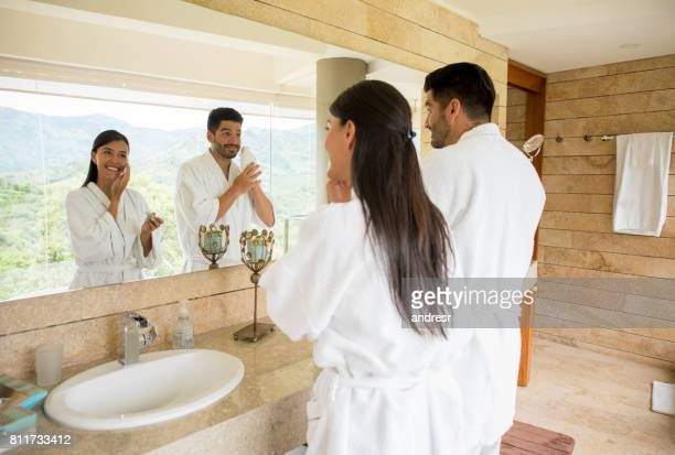 couple in the bathroom following their morning routine - grooming product stock photos and pictures