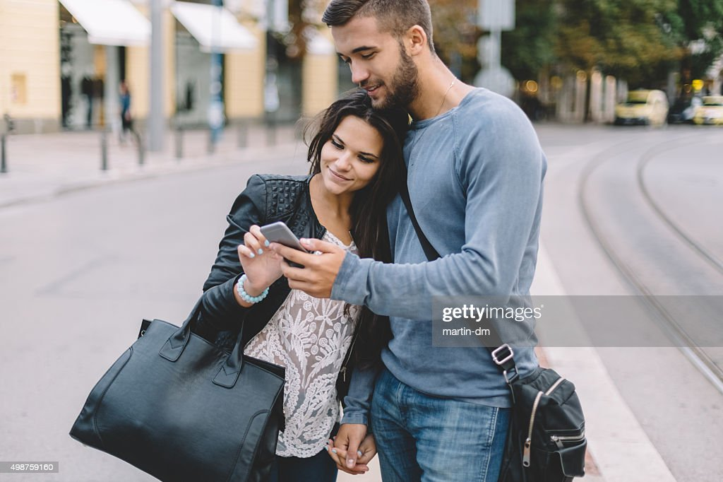Couple in the city using smartphone : Stock Photo