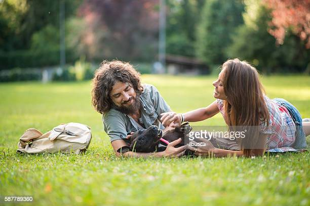 Couple in the park: Laying on grass with dog
