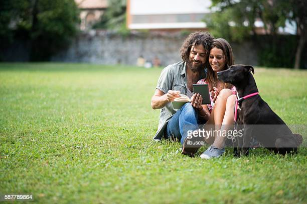 Couple in the park: Reading book and using e-reader