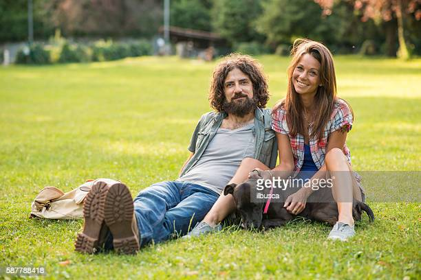 Couple in the park: Sit on grass with dog