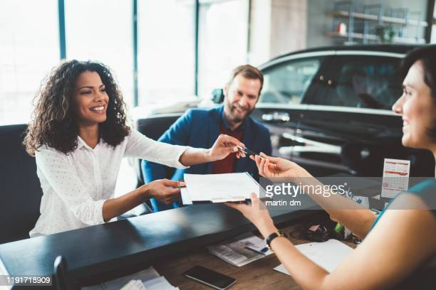 couple in the showroom buying new car - buying a car stock pictures, royalty-free photos & images
