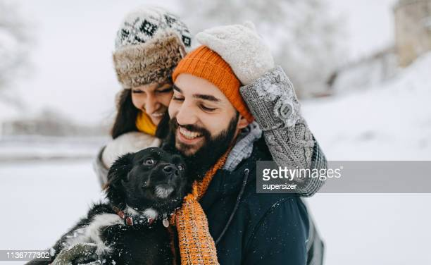 couple in the snow play with dog - warm clothing stock pictures, royalty-free photos & images