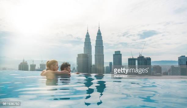 casal na piscina com a vista deslumbrante de kuala lumpur - torres petronas - fotografias e filmes do acervo