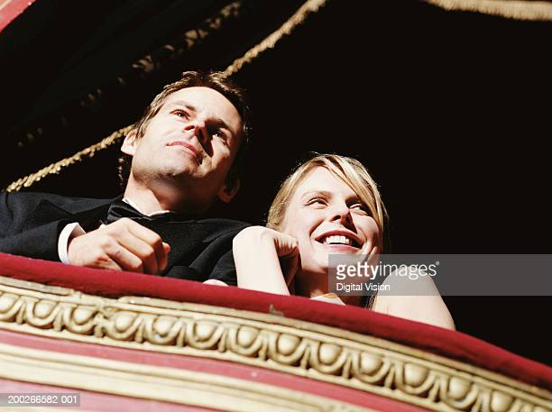 Couple in theatre box, smiling, low angle view