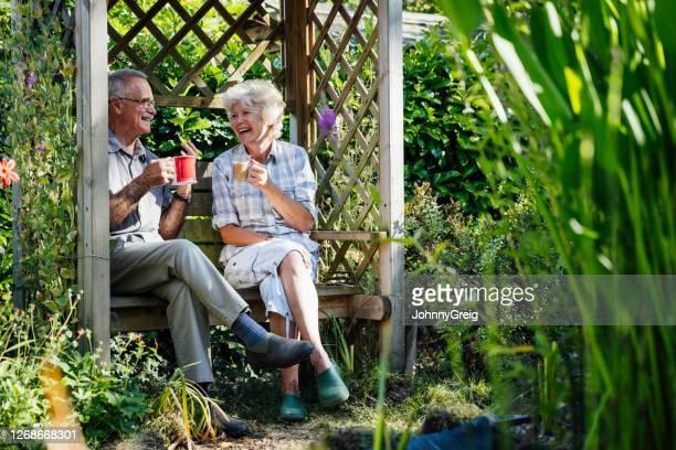 paar in hun jaren '60 die van koffie in binnenplaatstuin genieten - 65 69 jaar stockfoto's en -beelden