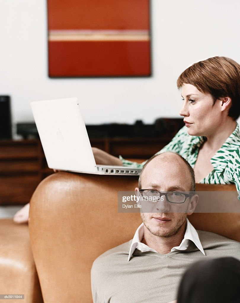 Couple in Their Living Room, Woman Sitting on the Sofa Using a Laptop : Stock Photo