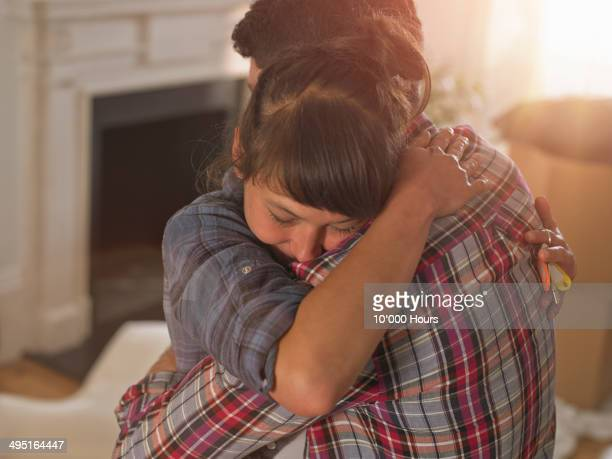 A couple in their new home hugging emotionally