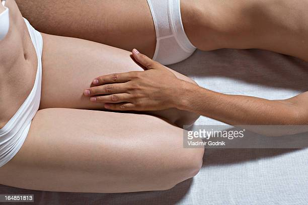 a couple in their underwear on a bed, close-up, midsection - man touching womans leg fotografías e imágenes de stock