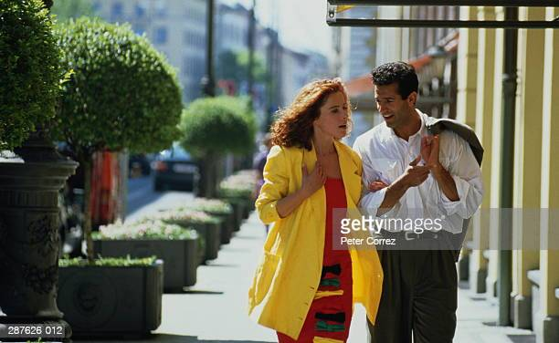 couple in town,woman in red dress and yellow jacket,man in suit - vestimenta de negocios fotografías e imágenes de stock