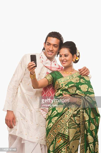 Couple in traditional clothing taking a picture of themselves