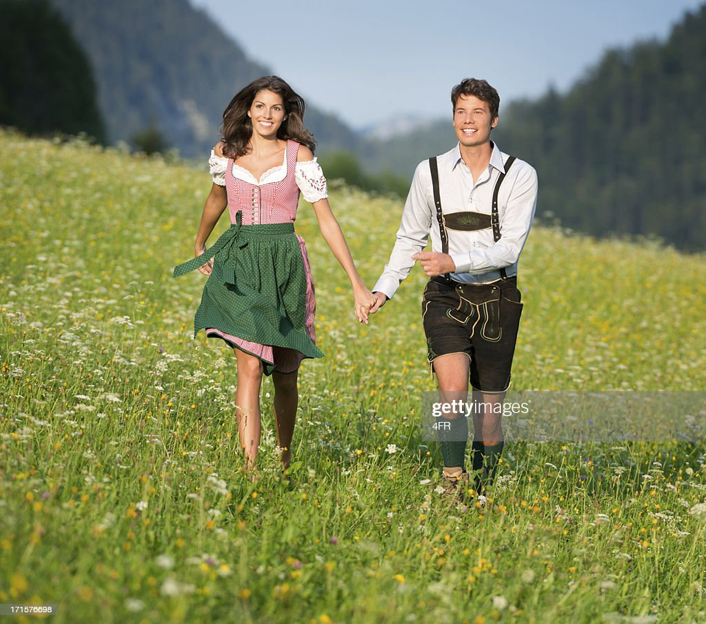 Couple in traditional Tracht running through the Meadows (XXXL) : Stock Photo