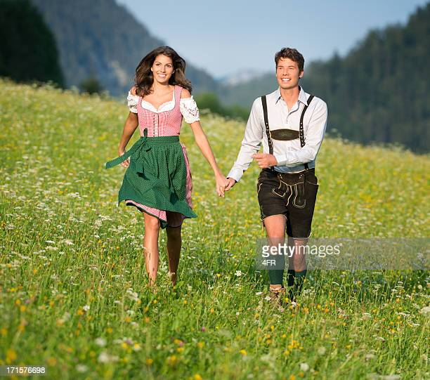 couple in traditional tracht running through the meadows (xxxl) - traditional clothing stock pictures, royalty-free photos & images