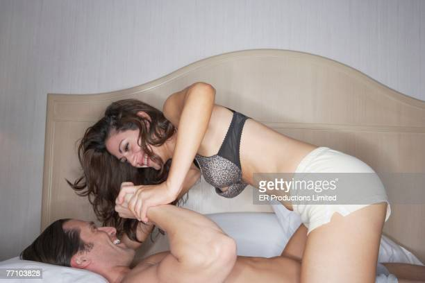 Couple in underwear wrestling on bed