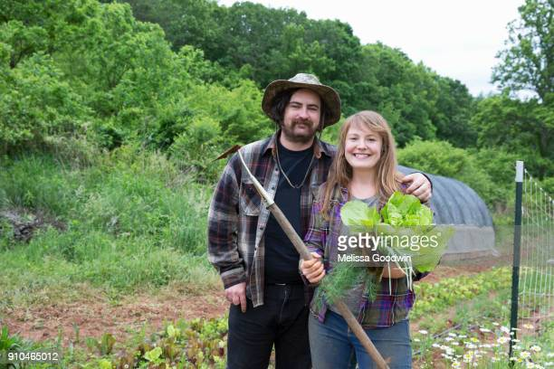 Couple in vegetable garden looking at camera smiling