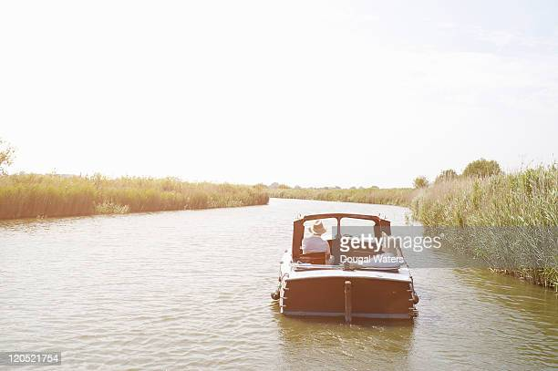 Couple in vintage boat on river.