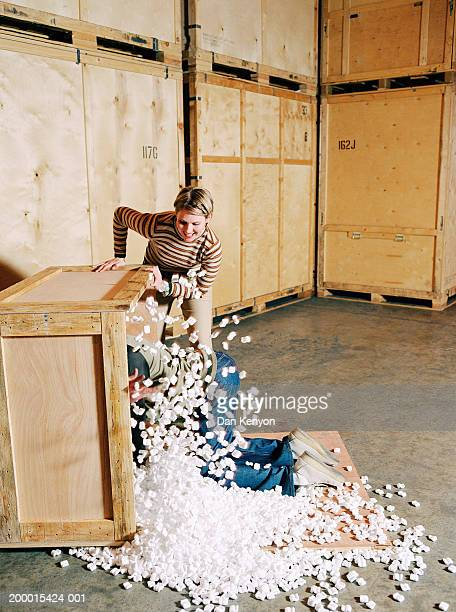 Couple in warehouse, man throwing packing foam from crate