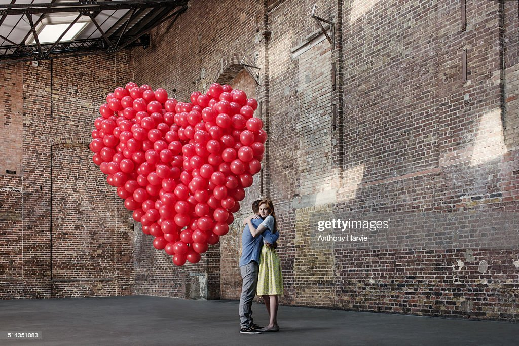 Couple in warehouse with heart made of balloons : Stock Photo