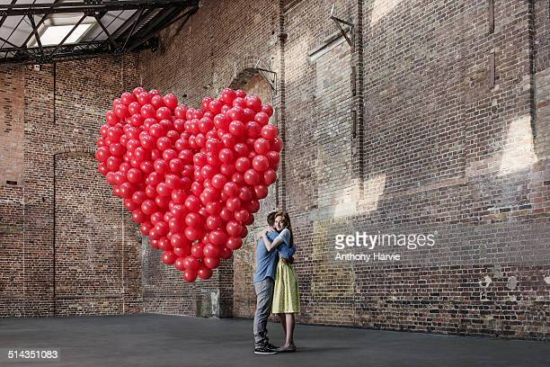 Couple in warehouse with heart made of balloons