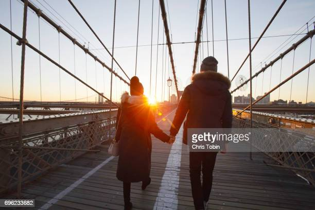 Couple in winter clothing holding hands on Brooklyn Bridge at sunset