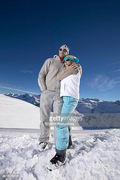 Couple in Winter Clothing Standing on a Mountain
