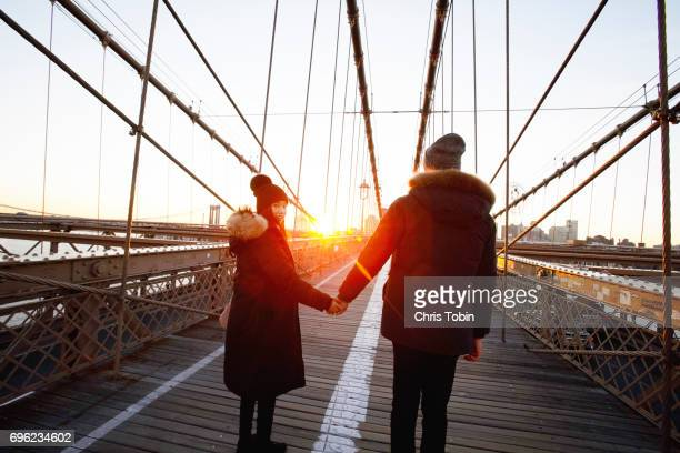 Couple in winter coats and hats holding hands on Brooklyn Bridge at sunset