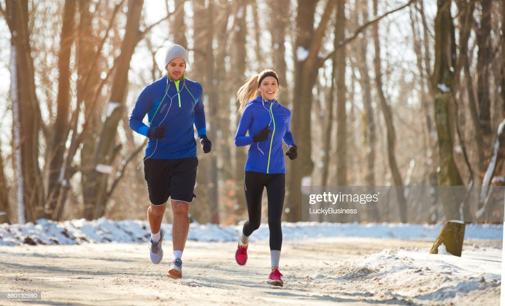 Couple in winter running together in nature : Stock Photo