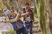 couple woodland throwing leaves