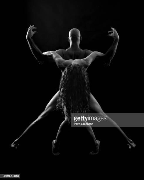 Couple in yoga pose, black background