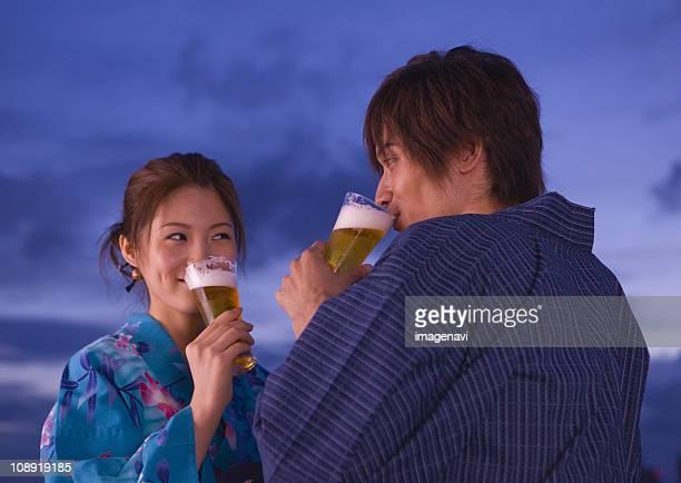 Couple in yukatas drinking beer