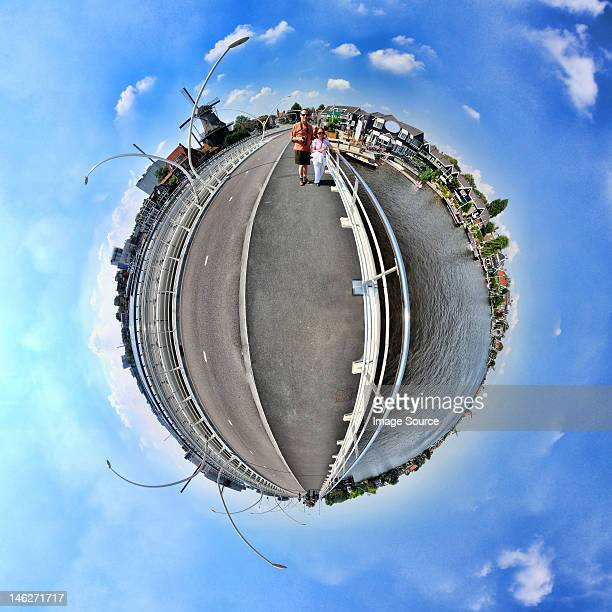 a couple in zaanse schans, netherlands, little planet effect - digital distortion stock photos and pictures