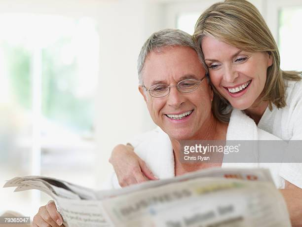 Couple indoors reading newspaper