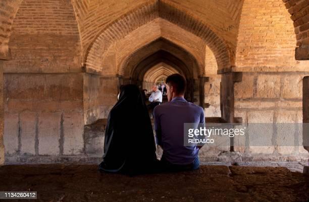 Couple inside the Khaju Bridge at Isfahan. Iran. Middle East.