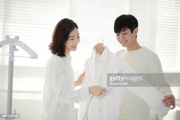 couple ironing shirt in living room - 白い服 ストックフォトと画像