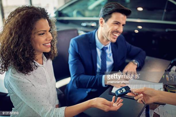 couple is buying new car and signing the contract and taking the car key - lease agreement stock photos and pictures