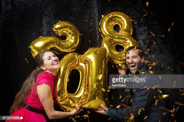 Couple is celebrating New year with glitter and ballon '2018'