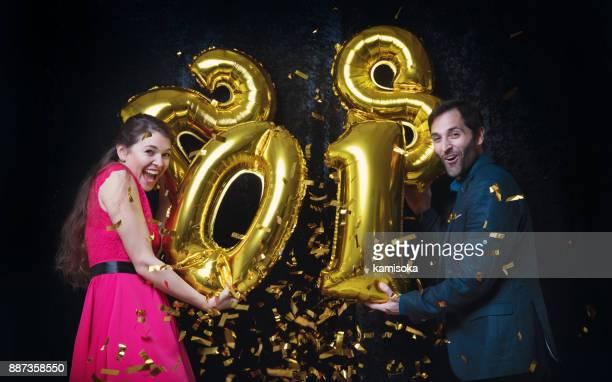 Couple célèbre réveillon avec paillettes et le ballon «2018»