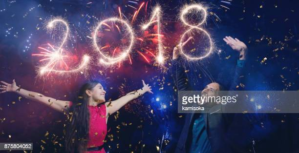Couple is celebrating new year's eve 2018 under fireworks