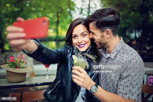 Couple is drinking cocktail from one glass and taking selfie