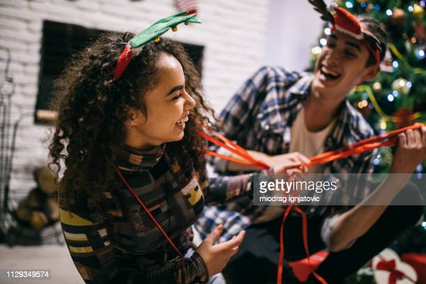 Couple is goofing around while wrapping gifts