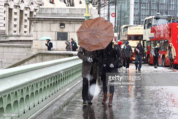 CONTENT] A couple is hiding from the wet snow with their umbrella on Westminster Bridge Central London December 2010