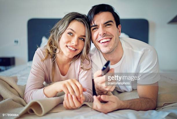 Couple is hugging and watching TV on the bed in the morning
