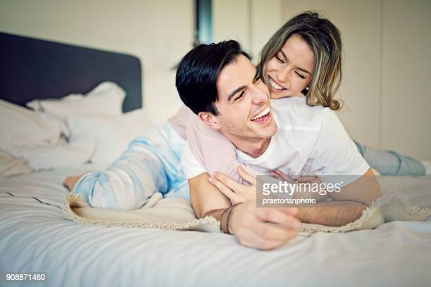 couple is hugging on the bed in the morning - good morning kiss images stock photos and pictures