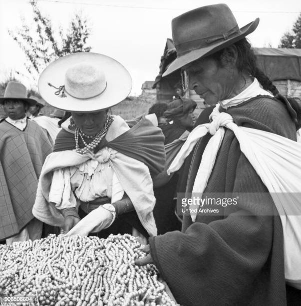 A couple is interested in the offer of bracelets at the market in the city of Otavolo Ecuador 1960s