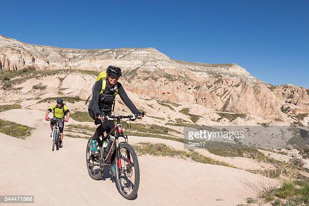 couple is mountainbiking in cappadocian canyons, turkey - tinted sunglasses stock pictures, royalty-free photos & images