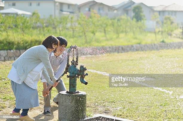 Couple is out the water in the well for hand pump