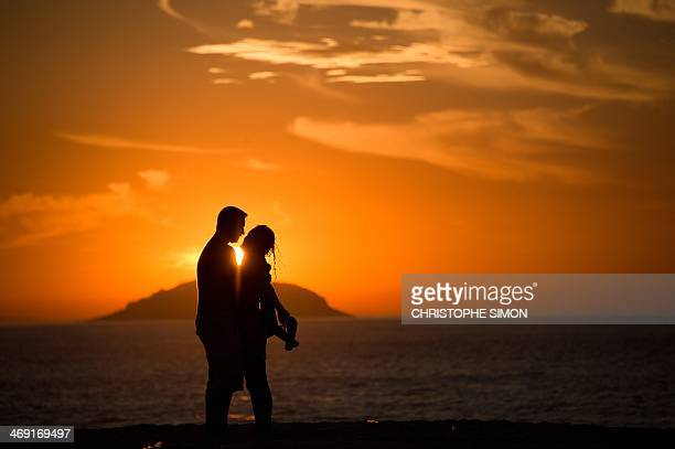 A couple is seen at the sunrise on Copacabana beach on the eve of Saint Valentin day in Rio de Janeiro on 13 februaryBrazil AFP PHOTO / CHRISTOPHE...
