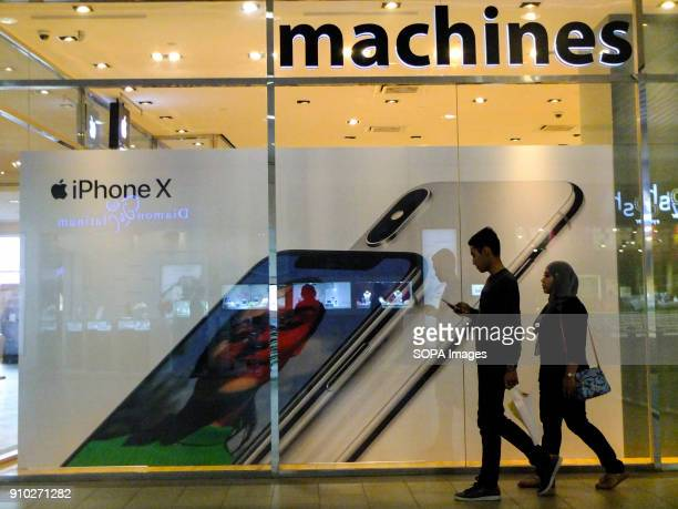 A couple is seen passing by the Apple Machine store at Kuala Lumpur Kuala Lumpur or commonly known as KL is the national capital for Malaysia and is...