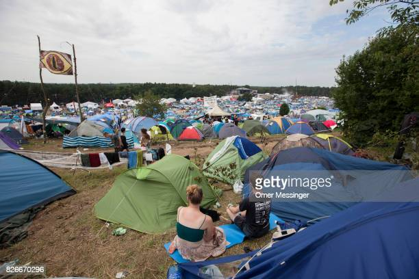A couple is seen sitting among tents at the 2017 Woodstock Festival Poland on August 4 2017 in Kostrzyn Poland The threeday rock music festival now...